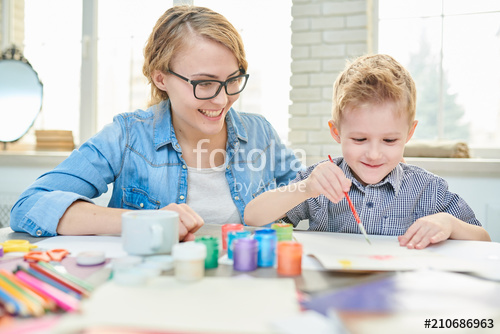 Portrait of happy young mother painting with her cute son sittin